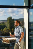 Handsome guy standing on balcony Stock Photos