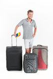 Handsome guy standing with luggage and smiling. Royalty Free Stock Image