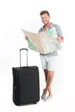 Handsome guy standing with luggage and smiling. Stock Images