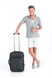 Handsome guy standing with luggage and smiling. Royalty Free Stock Images