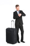 Handsome guy standing with luggage in suit. Royalty Free Stock Photos