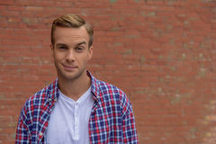 Handsome guy standing near brick wall stock photography