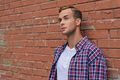 Handsome guy standing near brick wall Royalty Free Stock Photos