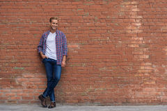 Handsome guy standing near brick wall. Strolling through town. Full growth photo of handsome guy leaning on brick wall, posing at camera and smiling Stock Images