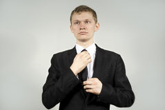 Handsome guy straightens his tie. In the background Stock Photography