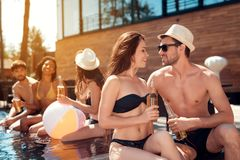 Handsome guy in summer straw hat flirts with girl in swimsuit sitting in pool. Swimming pool party. Stock Image