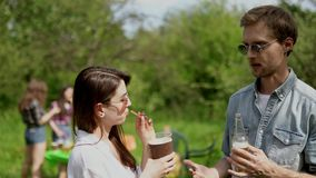 Happy guy talks with girlfriend while drinking at picnic in the park. Handsome Guy In Sunglasses Actively Gesturing And Drinking Beer While Talking With His stock video