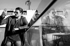 Handsome guy in sunglasses on the streets of the big city makes selfie. Reflection. Black and white photo. Stock Image