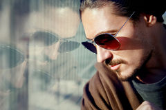 Handsome guy in sunglasses on the streets of a big city. Reflection Stock Image