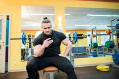 Handsome guy text messaging on his smartphone at gym. Handsome guy text messaging on his smartphone at gym Stock Photos