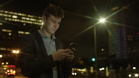 Handsome guy is typing a text message while standing on a street. Young handsome man is texting by using his iphone on a street at night stock footage