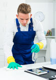 Handsome guy in uniform cleaning in office. Young male janitor dusting office desk and smiling indoors Stock Image