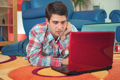 Handsome guy using laptop while lying on a floor Stock Image