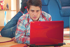 Handsome guy using laptop while lying on a floor Royalty Free Stock Photography