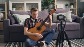 Handsome guy vlogger is recording video for subscribers teaching to play the guitar holding musical instrument and. Talking. Man is using camera on tripod at stock video