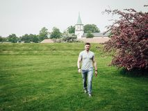 Handsome guy walking on a green field near a flowering tree. On a background of an old church Stock Photo