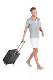 Handsome guy walking with luggage and smiling. Profile of man pulling bag on white background Stock Photography