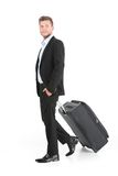 Handsome guy walking with luggage and smiling. Side view of young man on white background Stock Photography