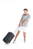 Handsome guy walking with luggage and smiling. Young man pulling bag on white background Royalty Free Stock Photos