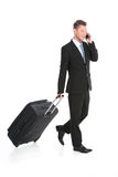 Handsome guy walking with luggage in suit. Stock Photography