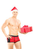 Handsome guy wearing red underpants and christmas hat holding a Stock Photo