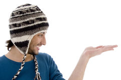 Handsome guy wearing woolen cap with open palm Royalty Free Stock Image