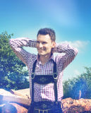 Handsome guy wears a Lederhosen and poses outside Royalty Free Stock Photos