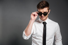 Handsome guy in white shirt standing and posing with sunglasses Stock Photo