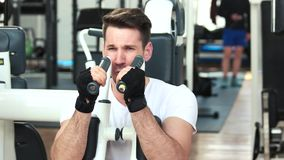 Handsome guy in white shirt training at gym. stock footage