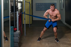 Handsome Guy Working Out With Rubber Band Royalty Free Stock Image