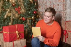 Handsome guy is writing a letter to Santa sitting under the tree surrounded by boxes of gifts. Christmas and gifts stock photography