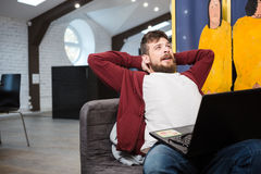 Handsome guy yawning while working on laptop at office Royalty Free Stock Photos