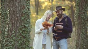 Handsome guy and young woman in autumn park. Young hippie couple on nature background. Love and romantic date concept.