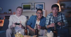 Handsome guys enjoying video game at home doing high-five having fun at night. Handsome guys joyful friends are enjoying video game at home doing high-five stock footage