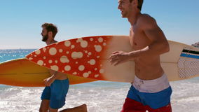 Handsome guys running at the beach stock video footage