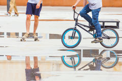 Handsome guys with skateboard and bicycle at freestyle park outdoors Stock Images