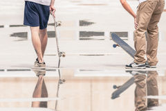 Handsome guys with skateboard at freestyle park outdoors. With beautiful reflection Royalty Free Stock Image