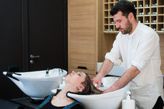 Handsome hairdresser washing female hair with concentration. He is holding a water tap. Woman leaning her head on sink. Handsome hairdresser washing female hair Royalty Free Stock Images