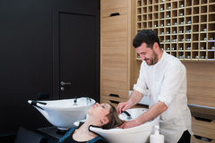 Handsome hairdresser washing female hair with concentration. He is holding a water tap. Woman leaning her head on sink. Handsome hairdresser washing female hair Stock Photography