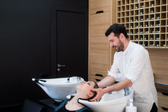 Handsome hairdresser washing female hair with concentration. He is holding a water tap. Woman leaning her head on sink. Handsome hairdresser washing female hair Royalty Free Stock Photos
