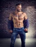 Handsome half-naked muscular man standing. Handsome muscular man with sweater open on naked torso, standing, in studio shot Stock Images