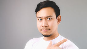 A handsome hand sign, pointing to the background. An asian man with white t-shirt and grey background royalty free stock images
