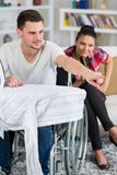 Handsome handicapped man in wheelchair watching tv with girlfriend Royalty Free Stock Photography