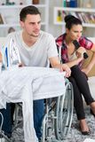 Handsome handicapped man in wheelchair watching tv with girlfriend Royalty Free Stock Images