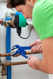 Handsome handyman turning off valves Stock Images