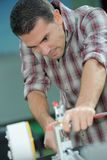 Handsome handyman working with electric planer in workshop. Man Royalty Free Stock Photo