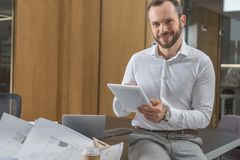 Handsome happy architect sitting on table with plans and using tablet. At office stock image