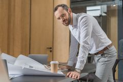 Handsome happy architect working with building plans. At office stock photo