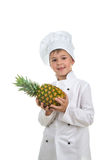 Happy handsome boy wearing chef uniform holding ananas. Handsome happy boy wearing chef uniform holding ananas. Portrait of a happy cute male child cook with Royalty Free Stock Image