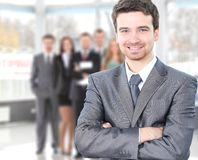 Handsome happy business man. With colleagues at the back Royalty Free Stock Image